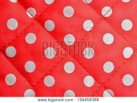 Background shot of a red polka dot canvas with seams.