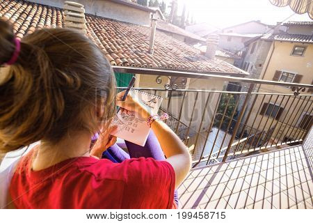 The girl sits on the terrace and draws a view of the city Tremosine. Italy