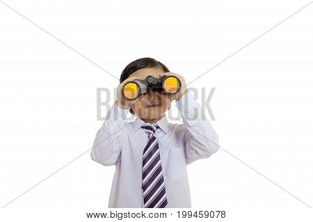 Image of little adorable boy looking through binocular in the studio isolated on white background