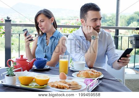 Bored Couple Using Smart Phone During Breakfast Time