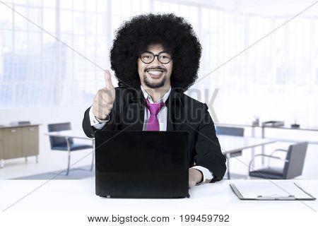 Young African businessman with curly hair showing thumb up while working with laptop computer in the office