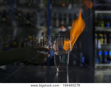 Barman's hands in bar interior making alcohol flaming cocktail. Professional bartender at work in bar mixing drink with burning fire.