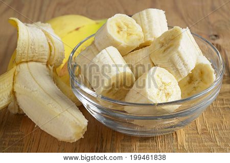 Sliced bananas in glass bowl on old wooden background