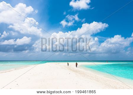 MAAFUSHI MALDIVES - FEBRUARY 29 2016: Amazing clouds during sunny day in a sandbank close to Maafushi in Maldives with few people