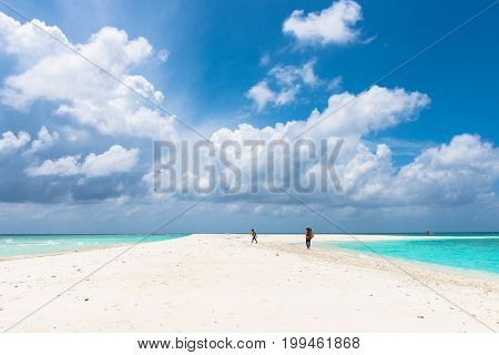 MAAFUSHI MALDIVES - FEBRUARY 29 2016: Wide angle picture of beautiful clouds in a sandbank close to Maafushi in Maldives with few people