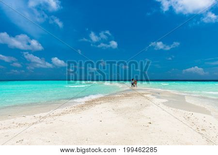 MAAFUSHI MALDIVES - FEBRUARY 29 2016: Few people enjoying sunny day in a sandbank close to Maafushi in Maldives with few people