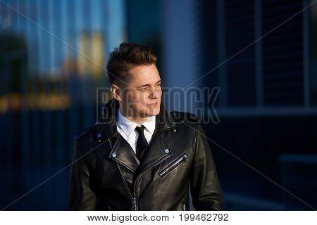 Outdoor shot of stylish young employee wearing leather jacket over formal clothes standing in urban surroundings going home on foot after working dat at office having happy expression on his face