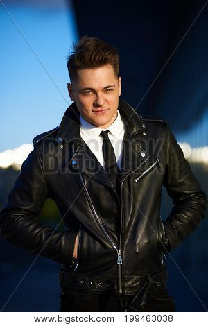 Urban style and street fashion concept. Outdoor picture of trendy-looking smooth-shaven young Caucasian man wearing stylish leather jacket over white shirt with black tie posing with hands in pockets