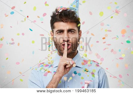 Attractive Bearded Young Caucasian Male In Blue Shirt Holding Index Finger At His Lips, Pronouncing