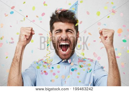 Joyful Bearded Man In Formal Clothes And Holiday Cap, Clenching His Fists With Happiness, Celebratin