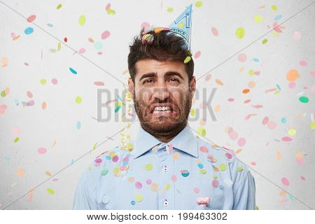 Horizontal Portrait Of Bearded Man Looking With Displeased Expression, Curving His Lips, Wearing For
