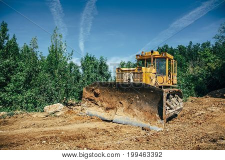 Big industrial yellow excavator or bulldozer on construction site, green trees and blue sky on foreground, copy space