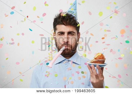 Displeased Unhappy Bearded Caucasian Man With Cone Hat On Head And Party Horn In Mouth Looking At Ca
