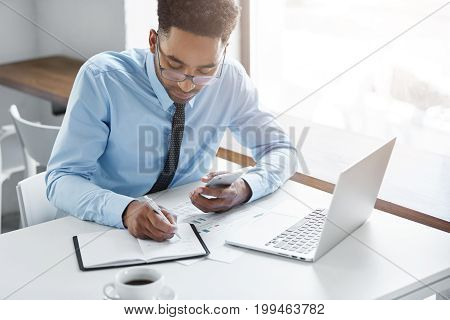 Concentrated Young Afro-american Financial Analyst In Glasses Holding Mobile Phone And Writing Down