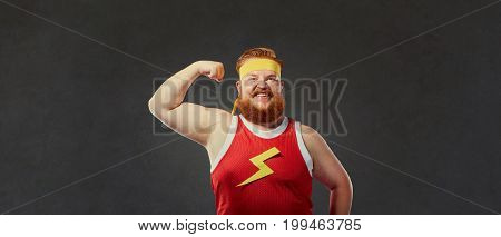A funny fat man in sports clothes shows a hand with muscles biceps. Concept of sport.