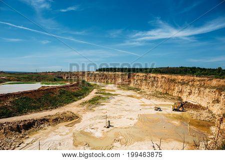 Panoramic photo of big yellow quarry, limestone mining concept
