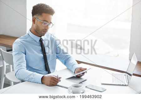 Picture Of Unshaven Young Male African Salesman In Formal Wear And Glasses Sitting At Cafe Table Wit
