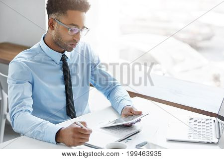 Attractive Buisnessman Sitting In Office, Writing Something In His Pocketbook And Looking In Electro