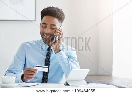 Young Mixed Race Businessman Wearing Official Clothes, Sitting At Spacious Office, Paying Bill With