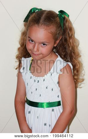 Pretty smiling curly little girl with white dress