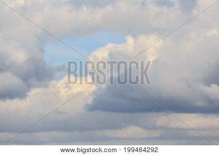 The clear blue sky break among the clouds at sunset as a background