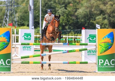TAGANROG ROSTOV-ON-DON REGION AUGUST 6 2017: Competitions in equestrian sport devoted to the Day of Liberation of the Neklinovskiy district. Young horsewoman in a white suit on sorrel horse jumps over an obstacle
