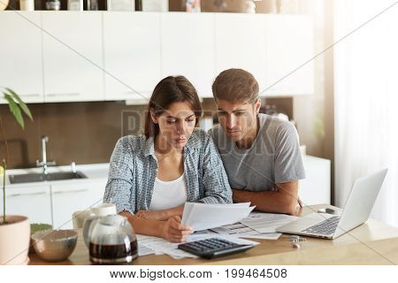 Busy Couple Having Financial Problems, Looking At Papers Sended From Bank, Asking Them To Pay Their