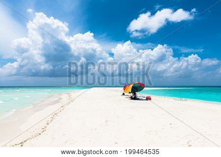 MAAFUSHI MALDIVES - FEBRUARY 29 2016: Amazing clouds during sunny day in a sandbank close to Maafushi in Maldives with native man under the umbrella