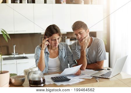Serious Man And Female Looking Attentively In Documents, Trying To Solve Their Financial Problems. Y