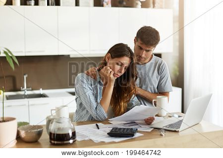 Beautiful Young European Couple Feeling Stressed Out Because Of Many Debts, Trying To Make Both Ends