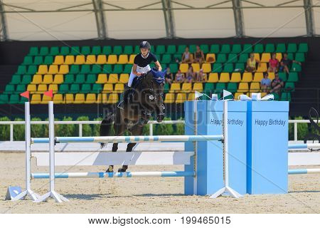 TAGANROG ROSTOV-ON-DON REGION AUGUST 6 2017: Competitions in equestrian sport devoted to the Day of Liberation of the Neklinovskiy district. Young rider on chestnut horse jumps over the barrier against the background of the spectators' grandstands