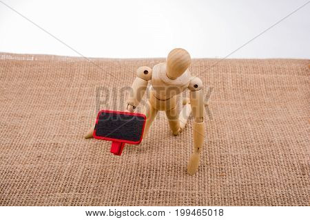 Wooden Man Holding A Notice Board In His Hand