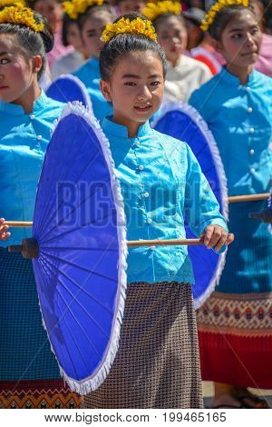 CHIANGMAI THAILAND - JANUARY 25 2015: Indigenous little girl with traditional costume holding blue umbrella and dancing in traditional style in parade of 22nd Traditional Skirt Fabric and The Indigenous Product and Culture Festival in Mae Chaem Chiangmai