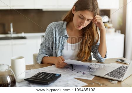 Indoor Shot Of Casually Dressed Young Woman Holding Papers In Her Hands, Calculating Family Budget,