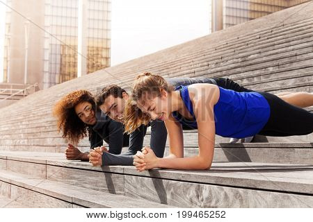 Portrait of multiethnic athletes holding elbow plank, standing together in a line outdoors at sunny day