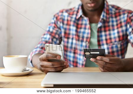 Close Up Shot Of Male Hands Holos Mug Debit Cad And Mobile Phone, Entering Data For Web-site Form, G