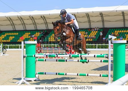 TAGANROG ROSTOV-ON-DON REGION AUGUST 6 2017: Competitions in equestrian sport devoted to the Day of Liberation of the Neklinovskiy district. The rider on horse jumps over the green barrier close-up