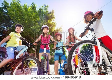 Group of multiethnic children in safety helmets, standing with their bicycles in summer park
