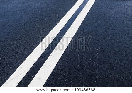 Double solid white line on wet asphalt