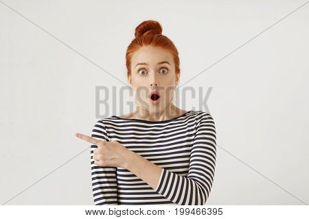 Amazed Female Model With Red Hair Tied In Knot, Wearing Stripe Clothes, Looking With Bugged Eyes And