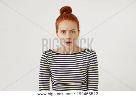 Grumpy Female With Red Hair Knot Looking Angrily Into Camera With Slightly Opened Mouth, Curving Her