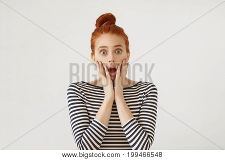Portrait Of Puzzled Woman With Ginger Hair Bun Feeling Fear, Keeping Hands On Cheeks, Looking With G