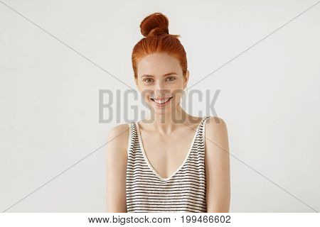 Happy Freckled Woman With Red Hair Knot, Wearing Loose Striped Shirt, Feeling Relaxation While Resti