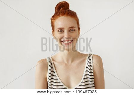 Glad Freckled Woman With Ginger Hair Knot, Wearing Striped Shirt, Isolated Over White Background. Ha