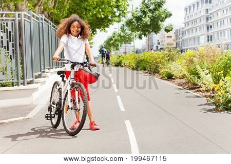 Full-length portrait of preteen African girl standing with her bicycle on the cycle lane at city park