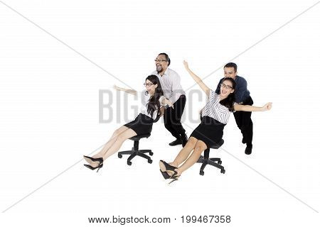 Image of two businessmen pushing their friends on the chair while racing in the studio