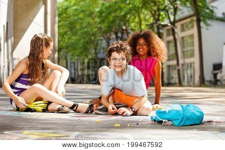 Group of diverse kids draw with color chalk on the street together