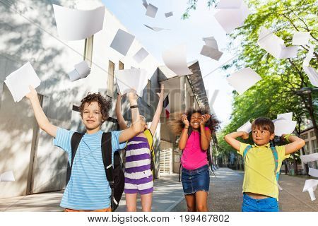 Group of French kids near the public school throwing paper sheets in the air happy and excited