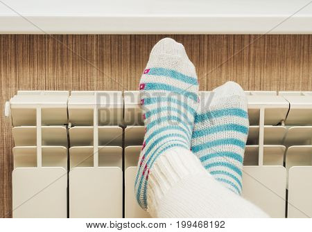 Female Feet On A Central Heating Radiator