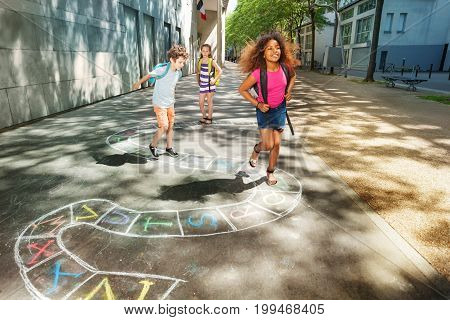 Group of kids jumping and paying hopscotch game outside near the school together